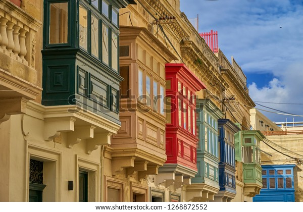 A row of traditional Maltese houses with enclosed Balconies, each painted brightly in a different colour.