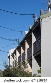 Row of traditional terrace houses in Australia with power lines connecting to central source