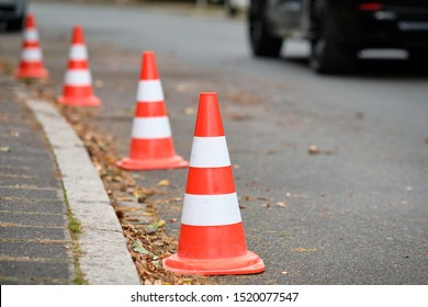 A row of traffic cones standing on a street along the curbstone of the pavement to prevent other people from parking their cars there. Seen in Germany