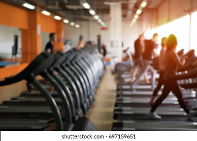 Row of treadmills in modern fitness center. Blurred picture of Running people. Gym equipment.