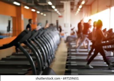 現代のフィットネスセンターの木の列。走る人のぼかした画像。体育用具。