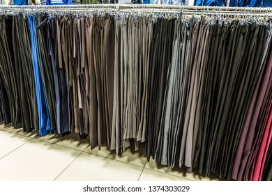Row of trousers hanging on trempels