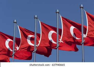 A row of Turkish flags flying against a blue sky.