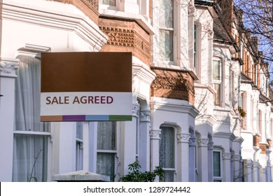 A row of typical British houses with 'sale agreed' estate agent sign