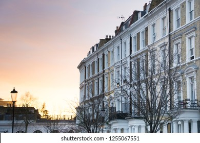 A row of typical townhouses in Kensington & Chelsea area of London with a sunset background