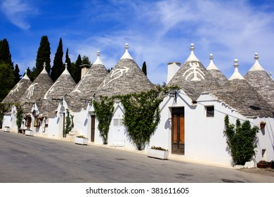Row of typical trulli houses in Alberobello, Puglia, Italy. Traditional symbols are painted on the conical roofs. A trullo is a traditional Apulian stone dwelling in Itria Valley.