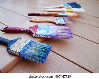A row of used, stained paintbrushes in various colors drying on a deck after a house painting project.