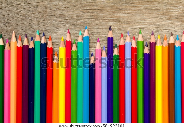 Row of various color pencil on wooden background