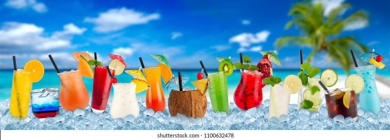 row of various colorful cocktails and long drink beverages in crushed ice cubes isolated on tropical palm beach ocean paradise background
