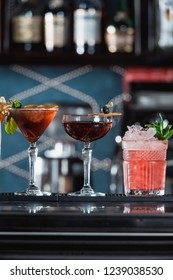 row of various colourfull alcoholic cocktails on a bar desk. Glasses of differen shapes