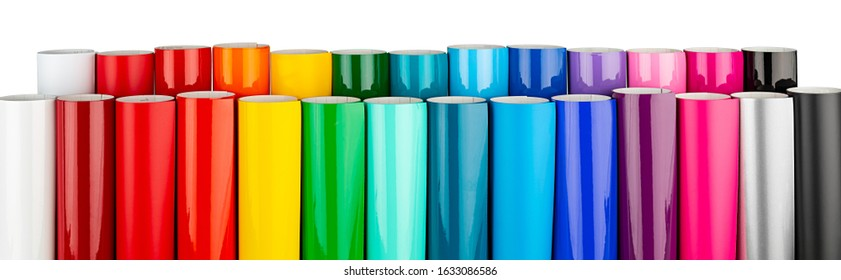 Row of various rainbow colored vinyl car wrapping or plotter cutting sticker foil film rolls isolated on white wide panorama banner background