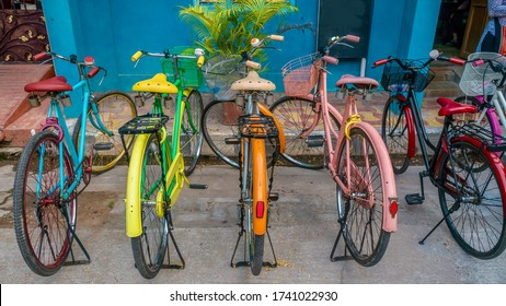 A row of vintage bicycles painted bright colors, parked on a street in Pondicherry, India.