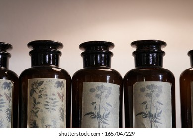A row of vintage brown glass apothecary jars with used labels displaying herbal drawings