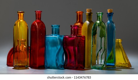 Row of vintage multicolored bottles from glass