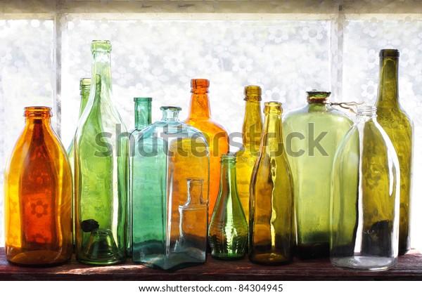 Row of vintage multicolored bottles on a windowsill
