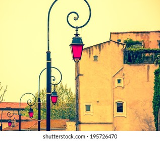 Row of vintage streetlights with magenta color glass on the street in Arles (Provence, France). Concepts of unique, different and standing out. Aged photo.
