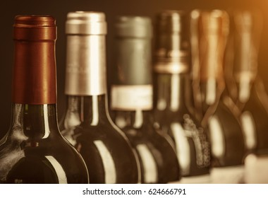 Row of vintage wine bottles with dry red  wine. Low depth of field. Tinted image.