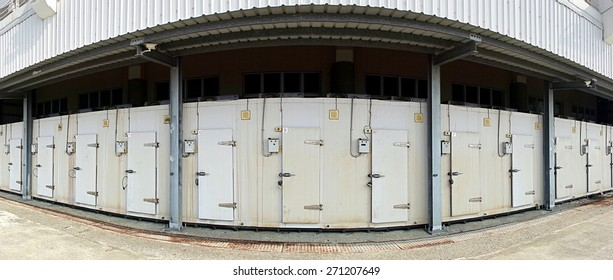 A row of walk-in refrigerators and freezer at a commercial cold storage facility