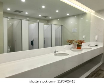Row of wash sink with big mirror in public toilet