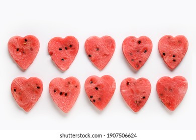 Row of watermelon slices as hearts on white background. Flat lay. Food Valentine day concept.