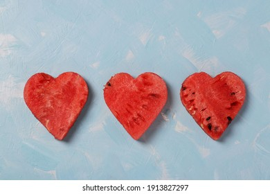 Row of watermelon slices as hearts on light blue background. Flat lay. Food Valentine day concept.