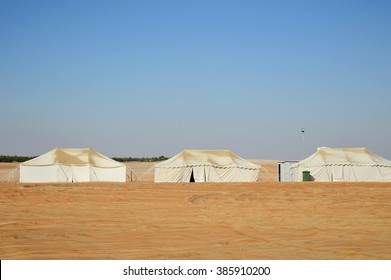 Row of white camp tents in desert
