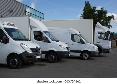 Row of white delivery and service van, trucks and cars in front of a factory and warehouse distribution plant