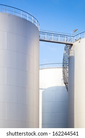 row of white diesel oil tanks of a refinery under a blue sky