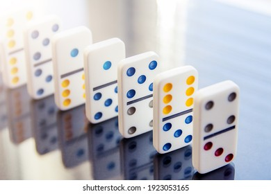 row of white dominoes on mirror surface. Selective focus