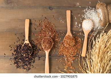 Row of white jasmine rice with various rice:  Rice berry, brown and thai red mixed rice on brown wooden background, organic and healthy food.