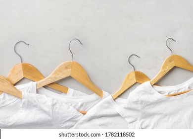 Row of white pure cotton wrinkly T-shirts hanging on wooden hangers on gray background. Casual unisex clothes natural materials shopping sale concept. Poster banner with copy space