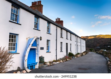 A row of white terraced cottages with an old boat seat at Boscastle in Cornwall