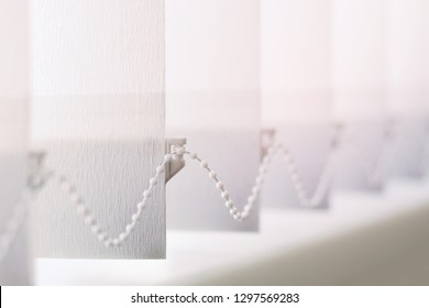 A row of white vertical blinds  cover the sunlight from the window. Close up.