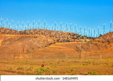 Row of wind turbines in California at sun set.