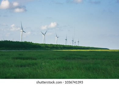 row of wind turbines in grassy field against sky,China.