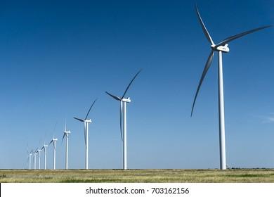 a row of wind turbines on a wind farm on the Texas Plains underneath a clear blue sky