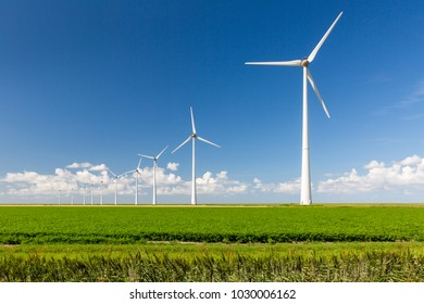 Row of wind turbines on a green field against a blue sky with distant puffy clouds
