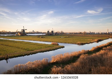 Row of windmills on the horizon with the vast Dutch flat landscape containing irrigation ditches in the orange sunset light and a blue sky