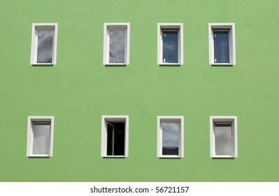 Row of windows on green wall of house