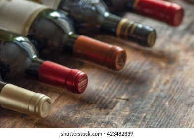 Row of wine bottles with dry red  wine on wooden background. Low depth of field.