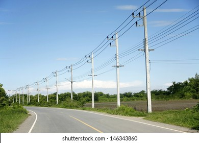 row of wire pole inside road on countryside with blue sky