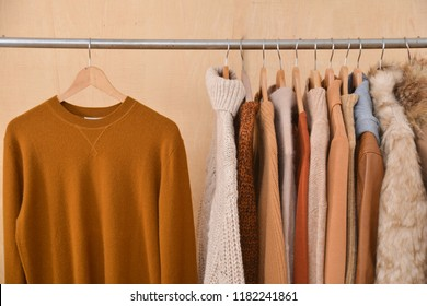 Row of women leather coat and jacket with sweater,fur coat on hangers isolated-wooden background