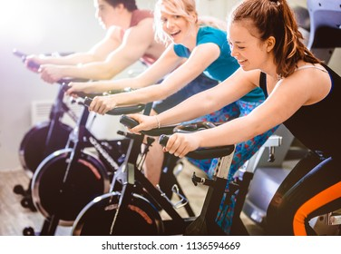 Row of women and man riding cycles in gym and smiling while working out in gym.