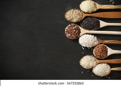 Row of wood spoons with various rice: white glutinous, black, basmati, brown and thai red mixed rice. Black wooden background, low light, top view.