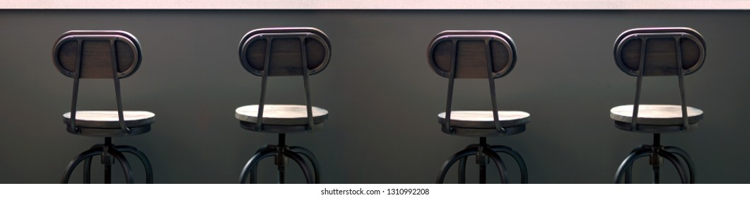 Row of wooden bar stools near the bar, dark background, two twin chairs