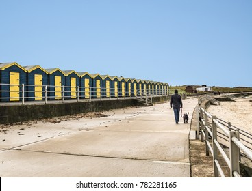 a row of wooden blue and yellow beach huts at Minnis bay, Thanet, kent uk on a promenade near a sany beach. A man is walking his dog on a leash. the sky is blue but it is winter and cold