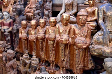 A row of wooden buddhist monks statues on sale at the handicraft market in Myanmar
