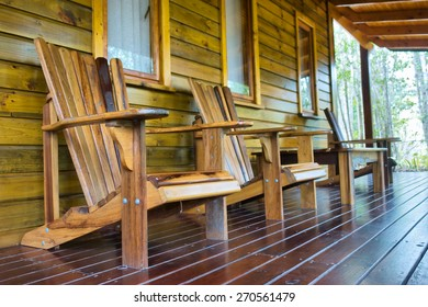 Row of wooden chairs on chalet terrace.