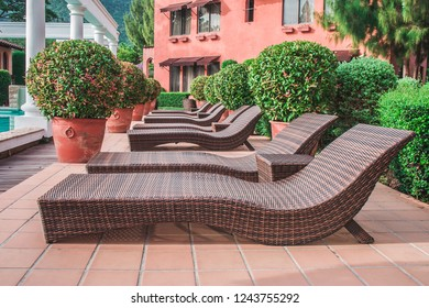 Row of wooden daybed place on concrete floor beside swimming pool in the resort.