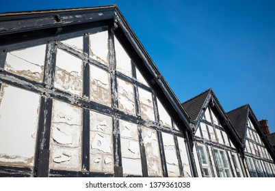 A row of wooden framed mock Tudor gable end in need of repair.